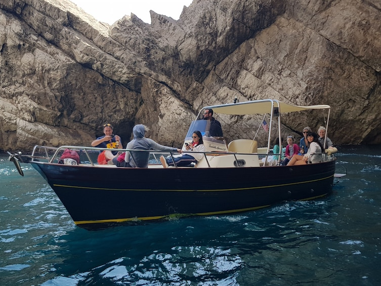 Show item 3 of 5. Group of tourists on a boat near Capri, Italy