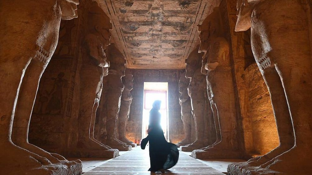 Show item 5 of 6. Person stands between large statues inside Abu Simbel Temples
