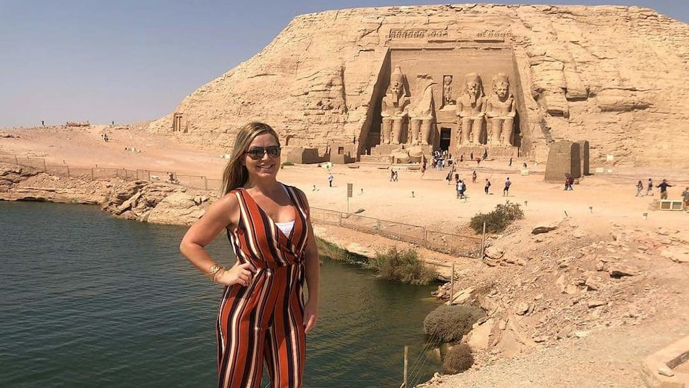 Show item 4 of 6. Woman poses in front of water and Abu Simbel Temples in Aswan, Egypt