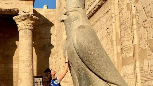 Woman touches bird statue at Temple of Horus at Edfu