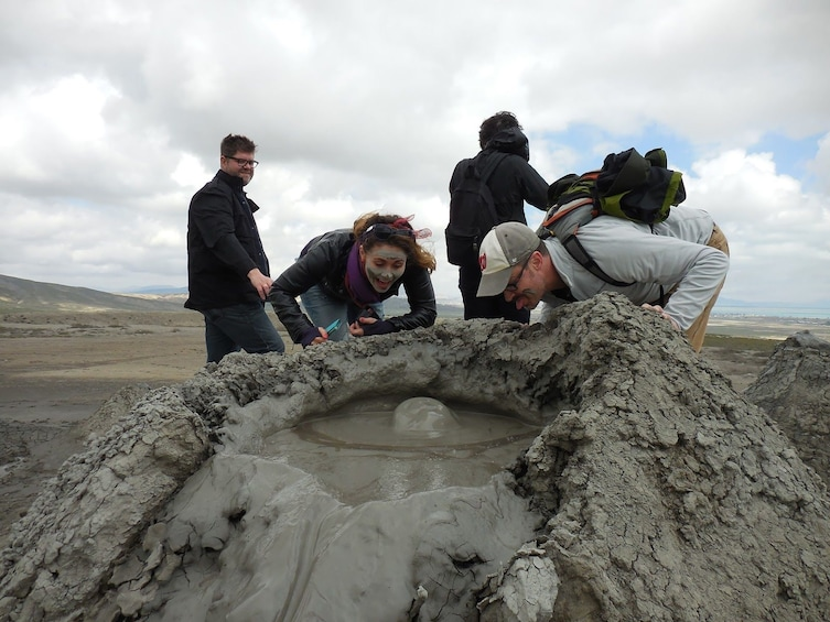 Show item 1 of 8. Tourists lean over mud volcanoes in Azerbaijan