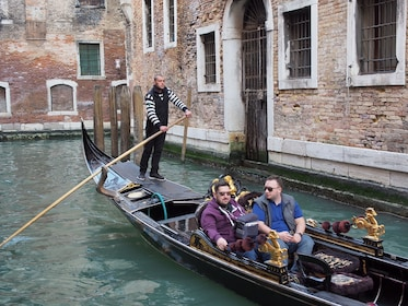 Tourists enjoying a gondola ride along the Venice canal