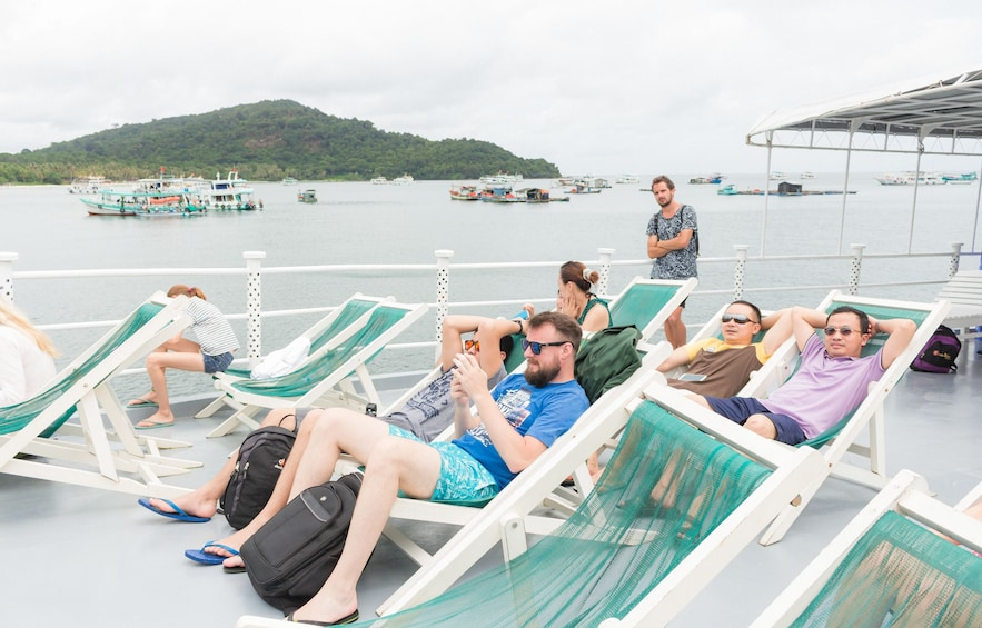 Show item 5 of 6. Tourists relax in lawn chairs on boat deck in Vietnam