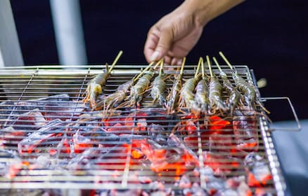 Hand turns small squid on sticks over coals