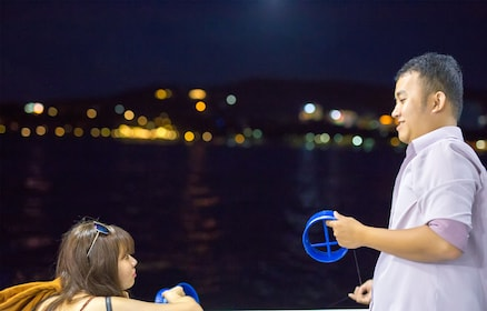 Man and woman hold spools of fishing wire on boat at night