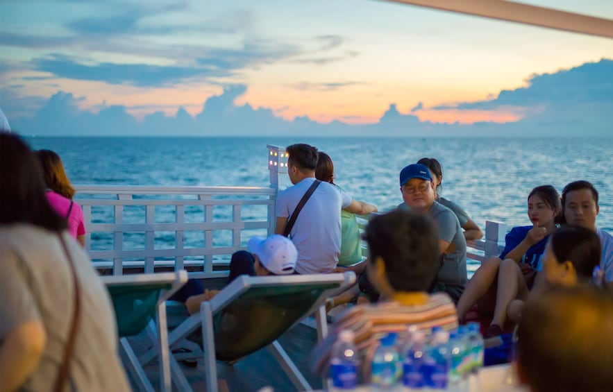 Show item 8 of 8. Group of tourists sit on deck in Vietnam at sunset