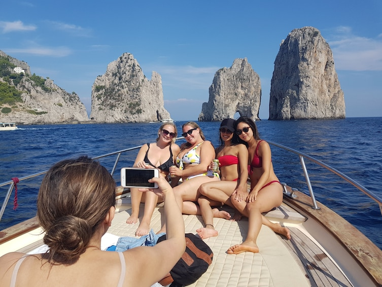 Show item 1 of 10. Friends pose for picture on deck of boat in front of Faraglioni rock stacks