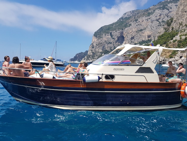 Show item 4 of 10. Tourists on a boat in the bright blue waters of Capri, Italy