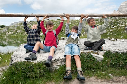 Children holding on to a wood rail in the Dolomites