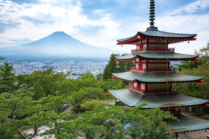 Pagoda surrounded by trees with Mount Fuji in the background