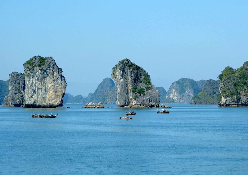 Show item 4 of 10. Small boats sail around islands of Halong Bay