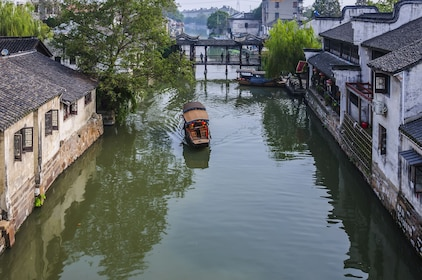 Small boat rides down canal of Zhouzhuang, China