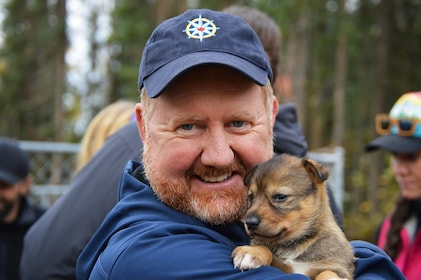 Man holding a puppy in Talkeetna