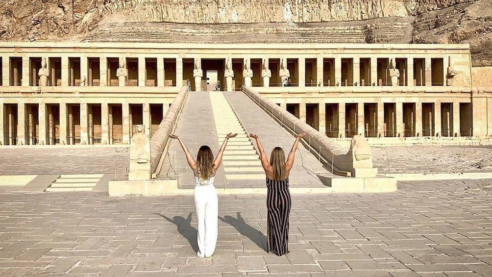 Two woman pose with hands in the air in front of the Mortuary Temple of Hatshepsut