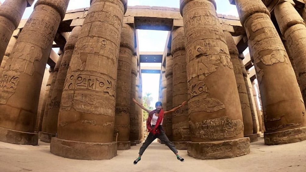 Woman jumps in front of large engraved columns in Egypt