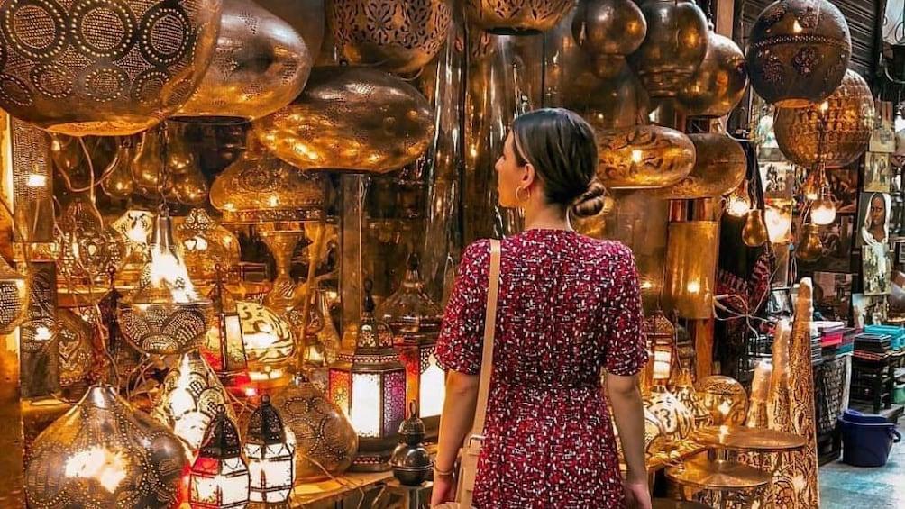 Woman looks around Khan el-Khalili at patterned metal lanterns