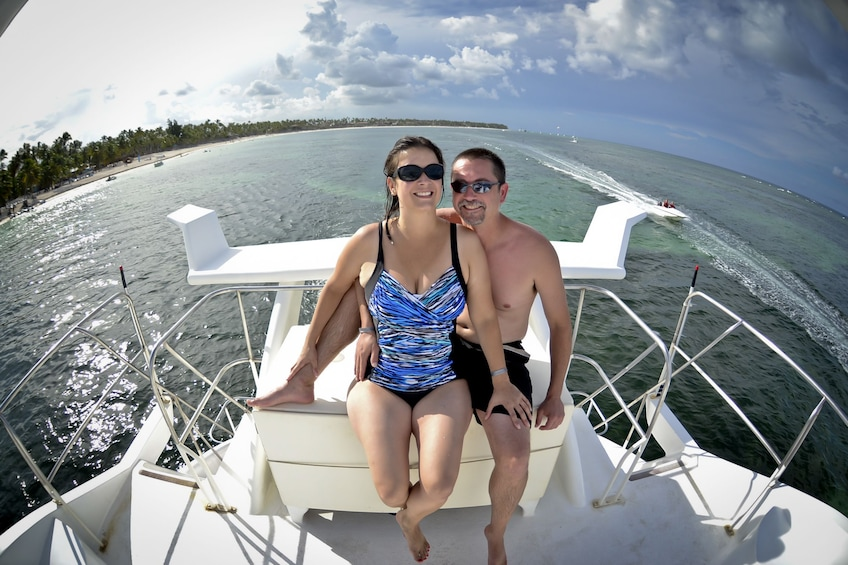 Show item 5 of 6. Couple in swimsuits pose on back of boat in Punta Cana