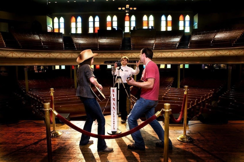 Show item 3 of 6. Tourists onstage at Ryman Auditorium in Nashville