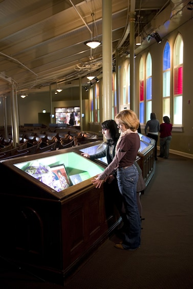 Show item 4 of 6. Women looking at artifacts at the Ryman Auditorium in Nashville