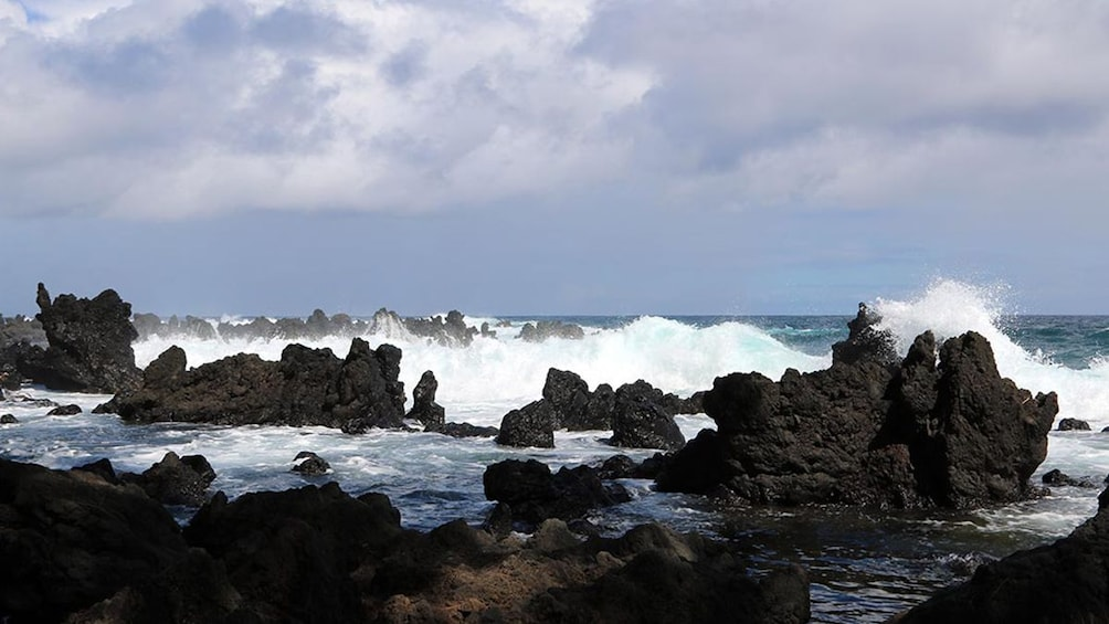 Show item 9 of 9. Waves breaking on black rocks on Maui