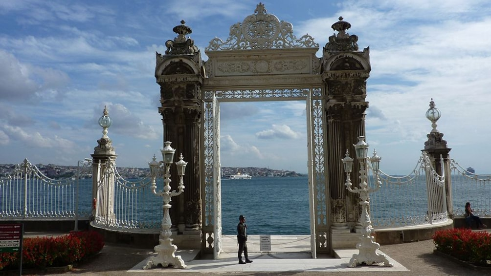 Show item 5 of 4. Large entry gate at Dolmabahçe Palace with view of water