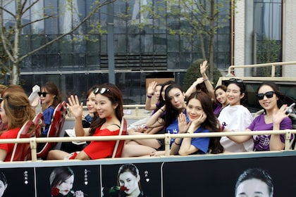 Tourists aboard the second level of a double-decker bus on tour in Shanghai
