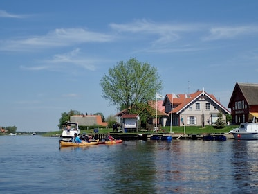 Group kayaking along a river during the day in Klaip?da