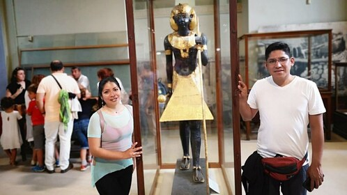 Man and woman pose with small pharaoh statue at the Egyptian Museum