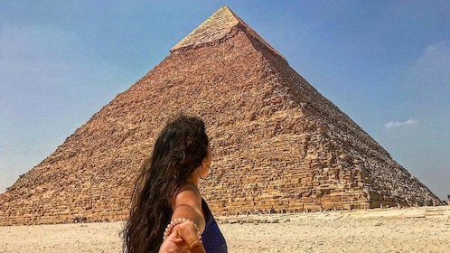 Woman leads partner towards the Great Pyramid of Giza