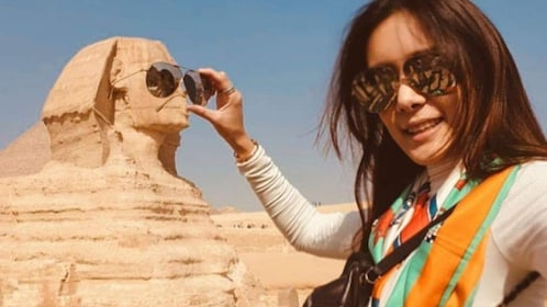 Woman puts her sunglasses over eyes of Sphinx in Giza, Egypt