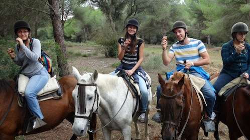Guests horseback riding while holding drinks in Jerez de la Frontera