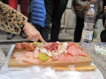 Hand points to charcuterie board in Lecco, Italy