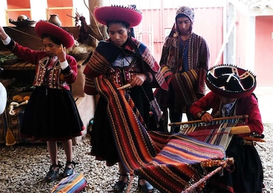 Women in traditional Peruvian dress weave colorful thread