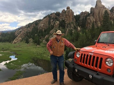 Man standing next to a Jeep in the heart of Colorado