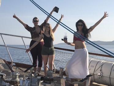 Women pose with arms above heads on boat in Mykonos, Greece