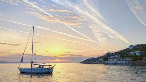 Boat approaches Mykonos at sunset
