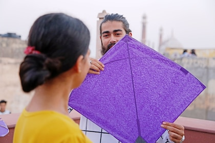 Man holding up a purple kite in Delhi