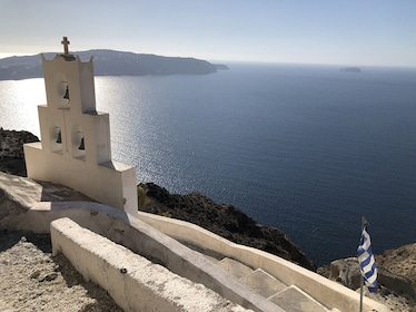 Small white monument with cross on the coast of Santorini