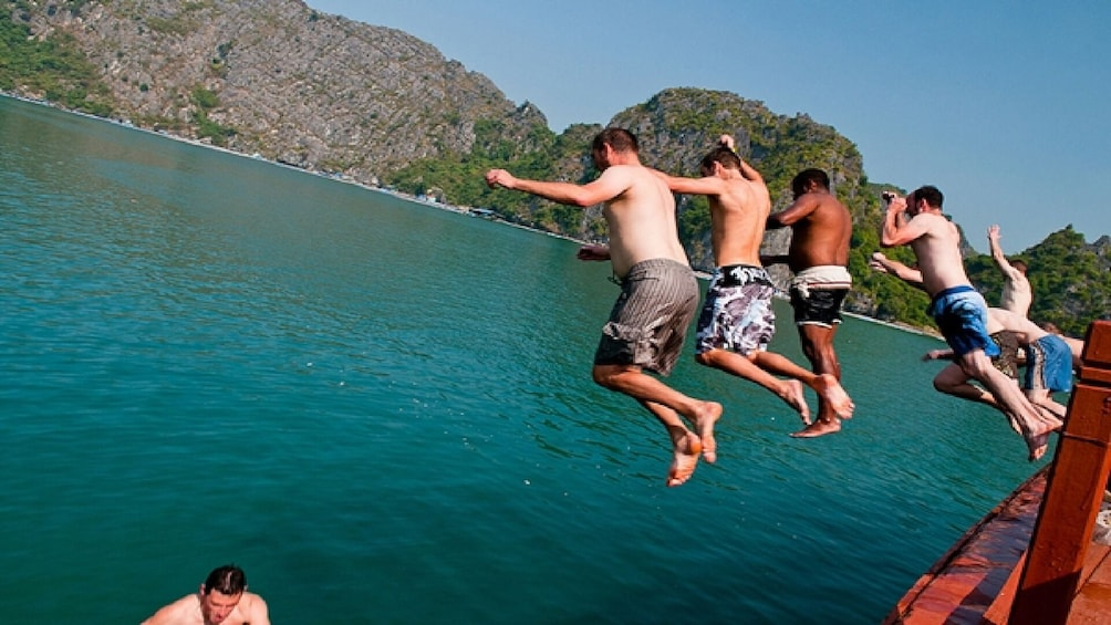 Show item 1 of 10. Friends jump off of side of boat into Lan Ha Bay, Vietnam