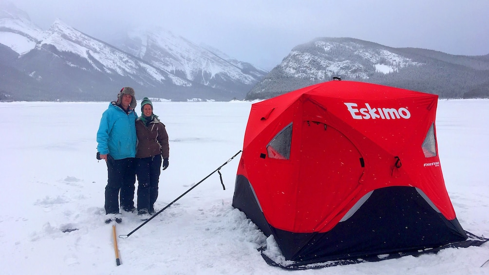 Show item 3 of 4. Two people stand next to a tent on a frozen lake