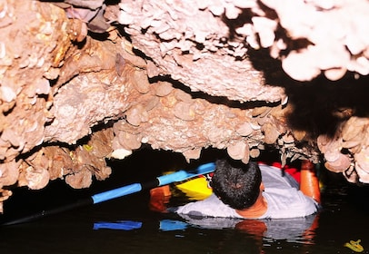 Group kayaking through limestone caves in Phang Nga Bay