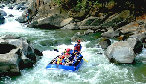 Boat floating down Mae Taeng River on a whitewater rafting adventure