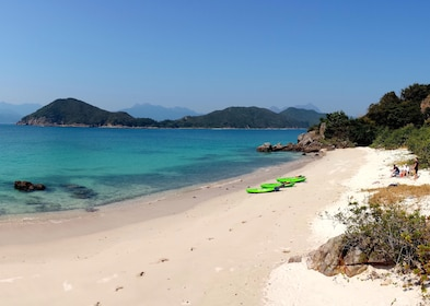 Day view of green kayaks on the beach at Hong Kong Geopark