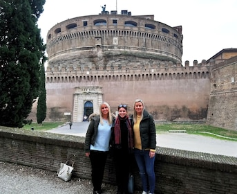 Tourists pose in front of the Castel Sant'Angelo