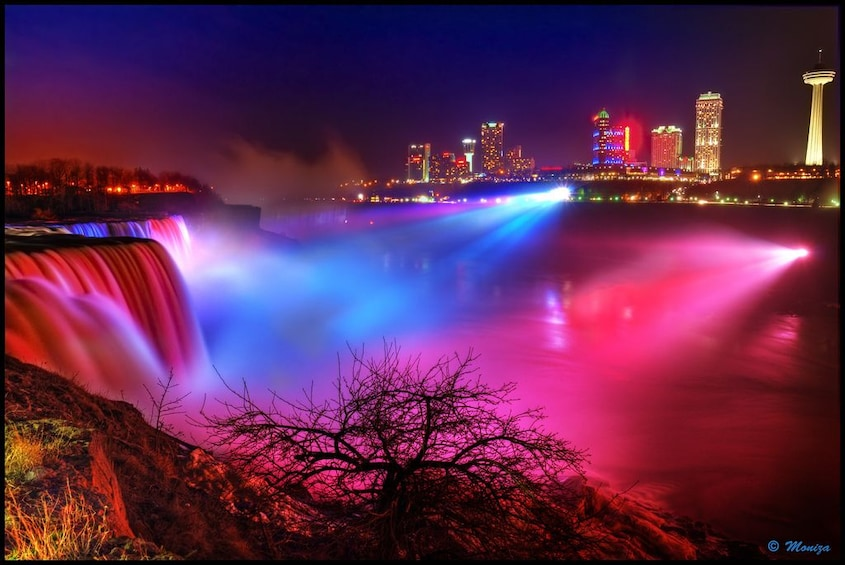 Show item 2 of 10. Red and blue lights shine on Niagara Falls