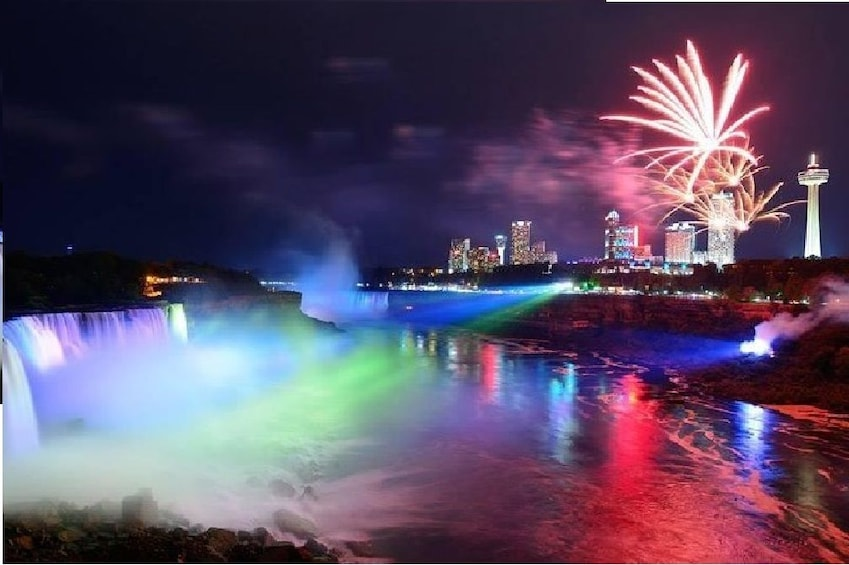 Show item 1 of 10. Niagara Falls lit up at night with firework show nearby