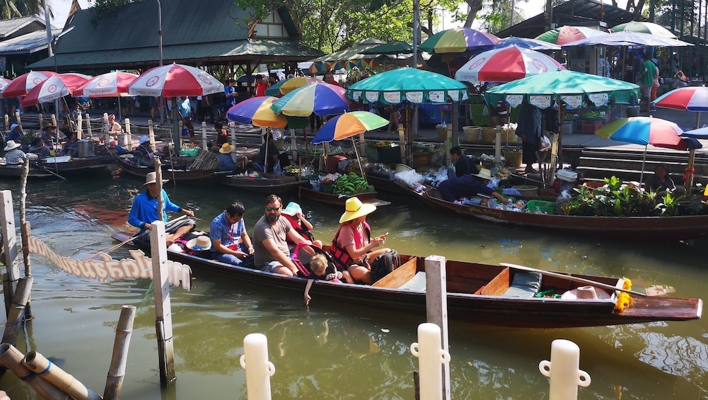 Show item 1 of 10. Boat of tourists riding through the Tha Kha Floating Market in Thailand