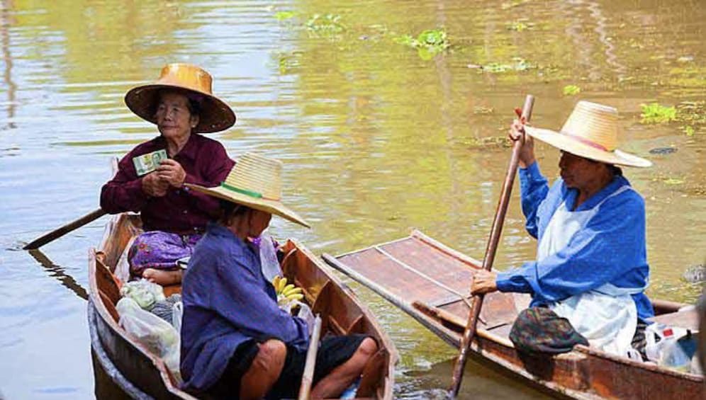 Show item 5 of 10. Three women in boats at Tha Kha Floating Market