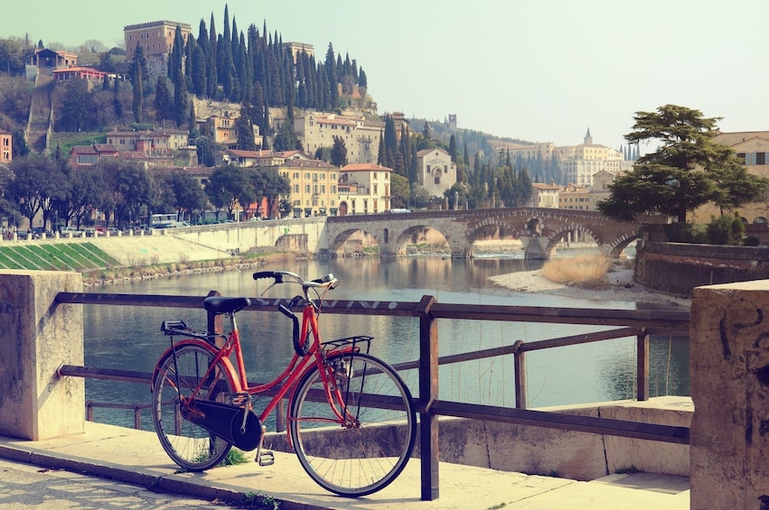 Show item 3 of 10. Bicycle parked over Adige River in Verona, Italy