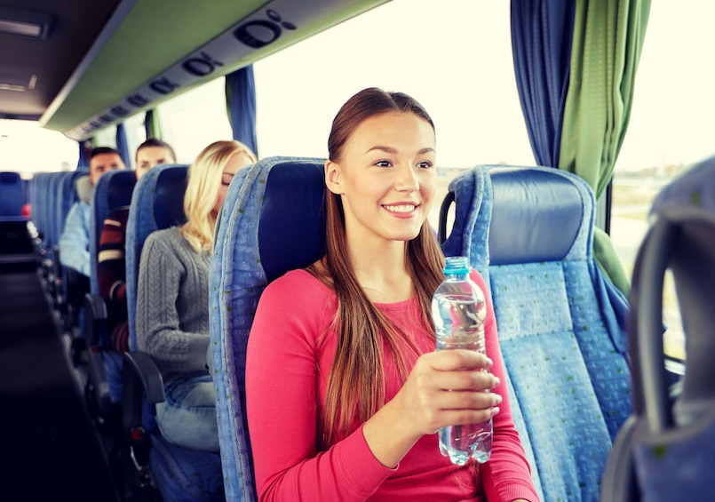 Show item 3 of 10. Woman with bottle of water smiles on bus to Niagara Falls
